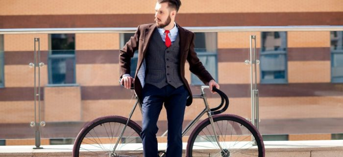 Handsome businessman in a jacket and red tie and his bicycle on city streets. red bag lies next. The concept of the modern lifestyle of young men
