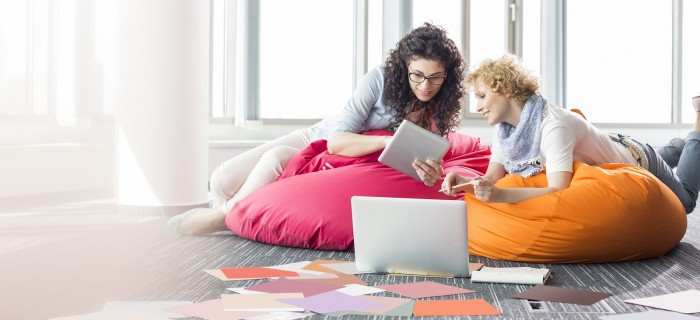 Creative businesswomen using tablet PC while relaxing on beanbag