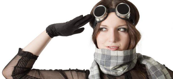 Prety pilot in scarf and googles saluting over white